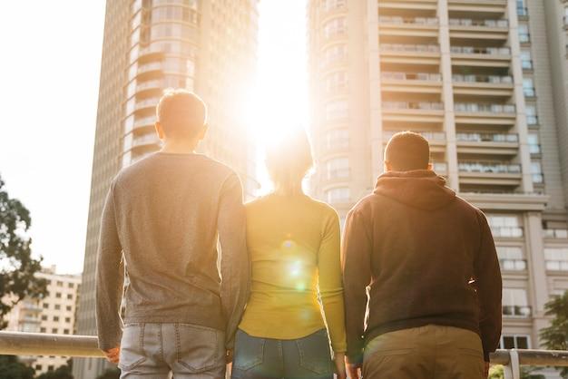 Giovani amici in piedi e guardando il tramonto