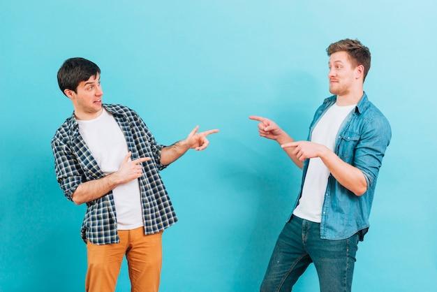 Giovani amici maschi facendo facce buffe che indicano le dita gli uni agli altri su sfondo blu