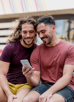 Giovani amici maschii che esaminano cellulare