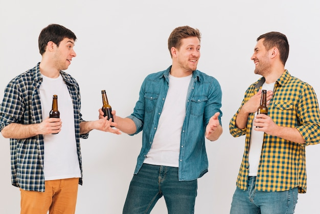 Giovani amici maschii felici che tengono bottiglia di birra a disposizione che rende divertente contro il contesto bianco