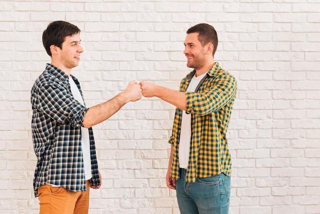 Giovani amici maschii sorridenti che stanno contro il muro bianco che batte il loro pugno