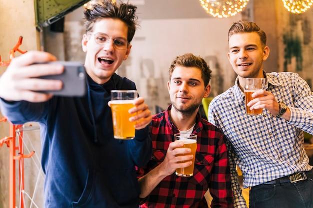 Giovani amici maschii sorridenti che tengono i vetri di birra che prendono selfie sul telefono cellulare