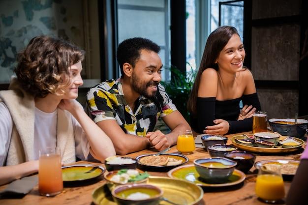 Giovani amici multietnici che celebrano qualcosa in un caffè