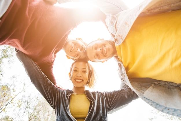 Giovani amici multirazziali che sorridono e che stanno nel cerchio