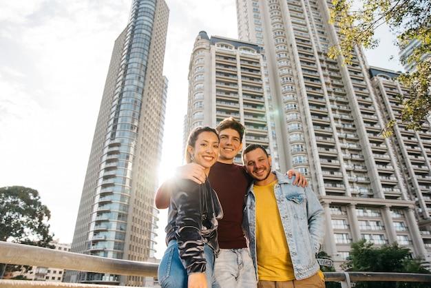 Giovani amici multirazziali in piedi contro edifici della città