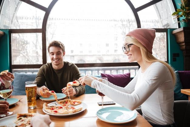 Giovani amici nel caffè mangiando pizza bevendo alcolici.