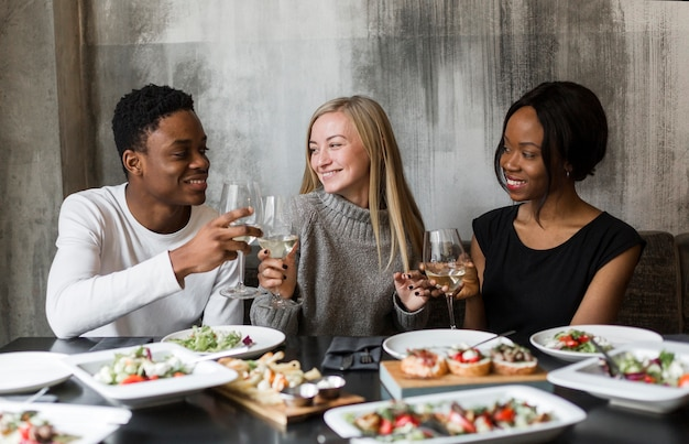 Giovani amici positivi che mangiano vino a cena