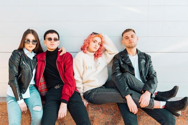 Giovani amici seri e stanchi che si siedono sul banco