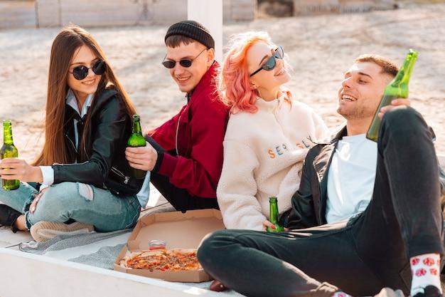 Giovani amici sorridenti che hanno festa all'aperto