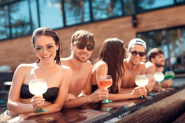 Giovani amici sorridenti con cocktail a bordo piscina