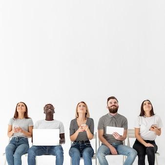 Giovani amici sulle sedie utilizzando dispositivi moderni