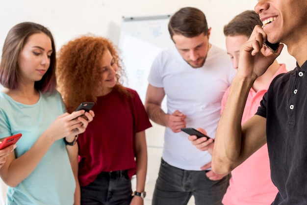 Giovani amici utilizzando smart phone per la comunicazione
