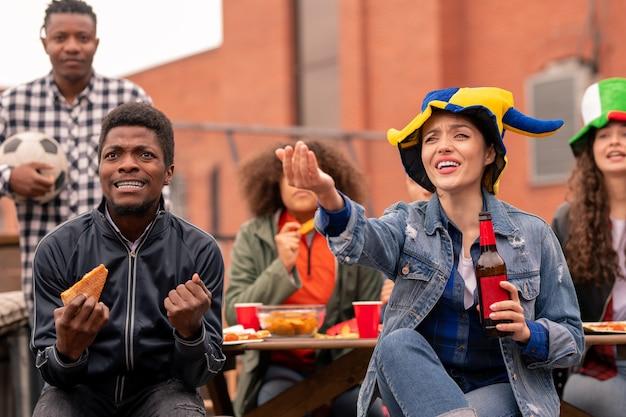Giovani appassionati di sport contemporanei con snack e birra guardando la trasmissione di calcio nella caffetteria all'aperto