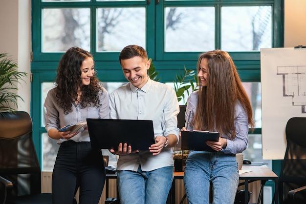 Giovani architetti o designer caucasici che utilizzano la tavolozza dei colori per il nuovo progetto sul computer portatile nell'ufficio moderno alla moda con la grande finestra.