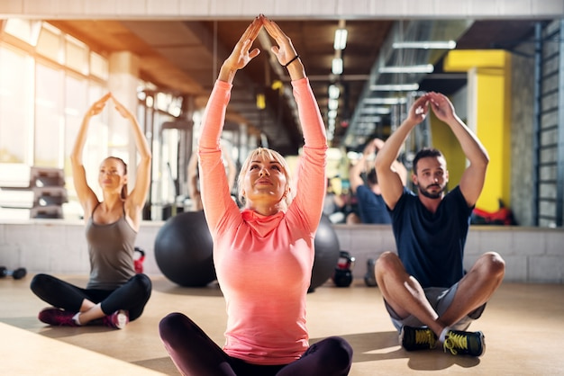 Giovani atleti stanchi in una palestra che allungano i muscoli dopo la lezione di pilates.
