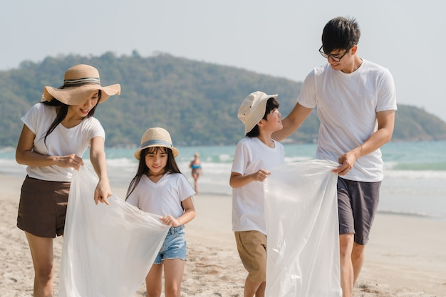 Giovani attivisti felici asiatici della famiglia che raccolgono rifiuti di plastica e che camminano sulla spiaggia. i volontari asiatici aiutano a mantenere la natura a ripulire la spazzatura. concetto sui problemi di inquinamento ambientale.