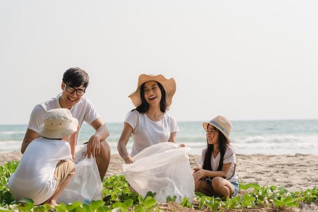 Giovani attivisti felici asiatici della famiglia che raccolgono rifiuti di plastica sulla spiaggia. i volontari asiatici aiutano a mantenere la natura pulita e a raccogliere i rifiuti. concetto sui problemi di inquinamento ambientale.