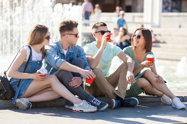 Giovani attraenti divertirsi insieme all'aperto. la gente che beve caffè e sorridente. gruppo di amici che camminano insieme.