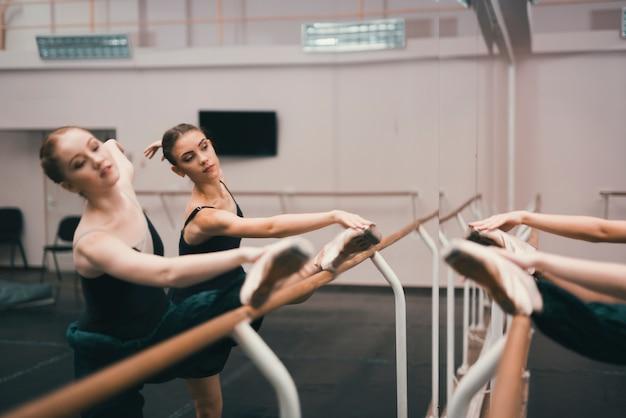Giovani ballerini classici femminili che praticano nello studio di danza