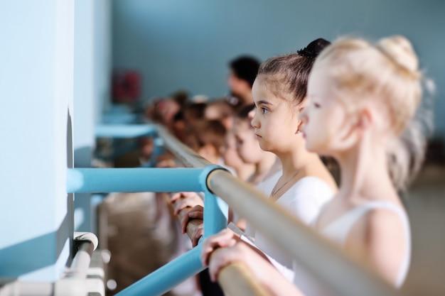 Giovani ballerini nello studio di danza. i giovani ballerini eseguono esercizi ginnici al balletto o alla sbarra mentre si scaldano in classe.