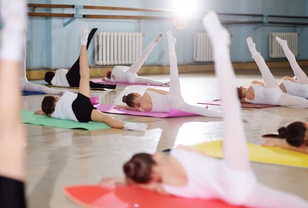 Giovani ballerini nello studio di danza. i giovani ballerini eseguono esercizi ginnici durante un riscaldamento in classe. sport, ginnastica, sviluppo del bambino