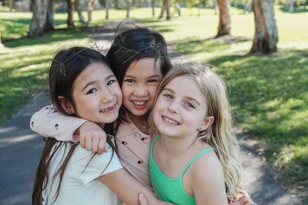 Giovani bambine etniche miste felici e sane che abbracciano e che sorridono nel parco, i migliori amici e l'amicizia