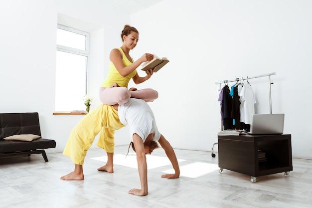 Giovani belle asana allegre di yoga del partner di addestramento delle coppie a casa.