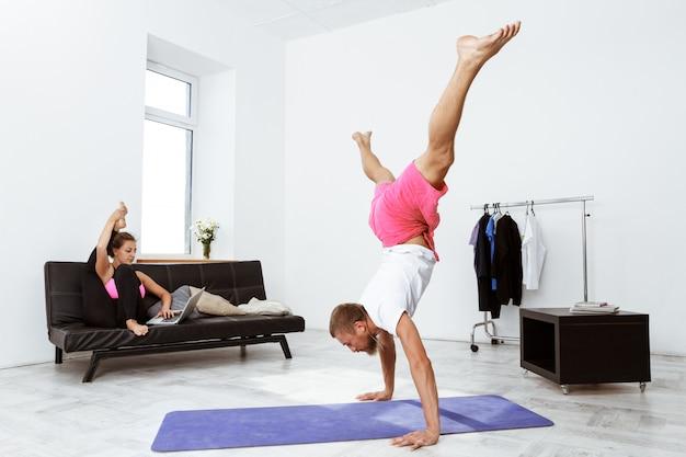 Giovani belle asana allegre di yoga di addestramento delle coppie a casa.