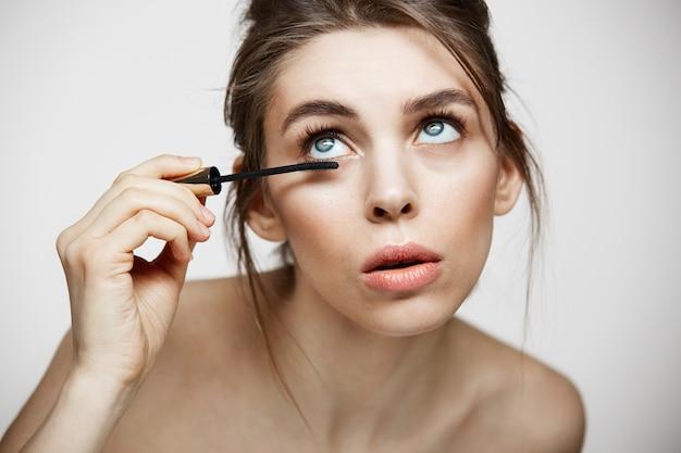 Giovani belle ciglia della tintura della ragazza sopra fondo bianco. concetto di salute e cosmetologia di bellezza. trattamento facciale.