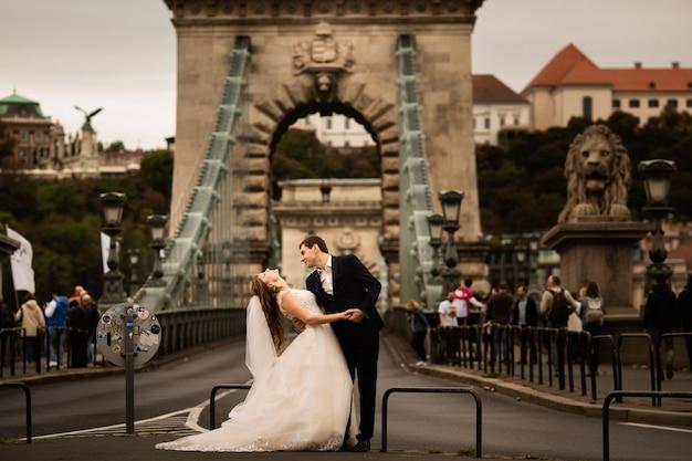 Giovani belle coppie alla moda delle persone appena sposate su un ponte a budapest, ungheria. bella donna in un abito da sposa bianco e bell'uomo in tuta.