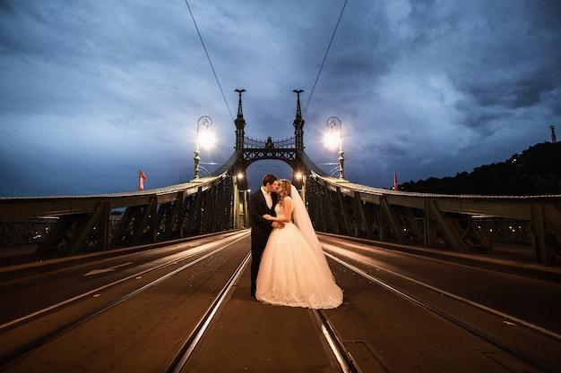 Giovani belle coppie alla moda delle persone appena sposate su un ponte a budapest