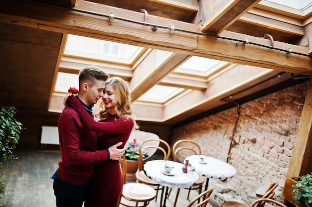 Giovani belle coppie alla moda in un vestito rosso nella storia d'amore al caffè vintage con grandi finestre sul tetto