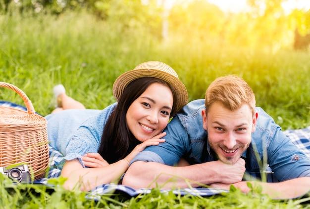 Giovani belle coppie che esaminano macchina fotografica e che sorridono sul picnic