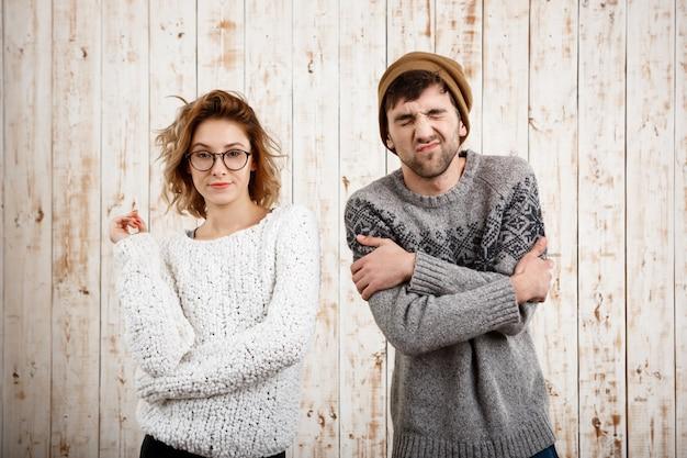 Giovani belle coppie che posano sopra la parete di legno