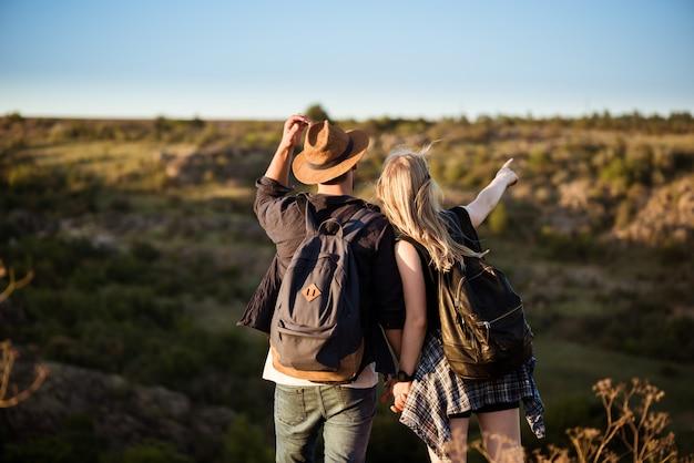 Giovani belle coppie che riposano, godendo della vista in canyon