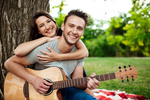 Giovani belle coppie che sorridono, riposando sul picnic in parco.