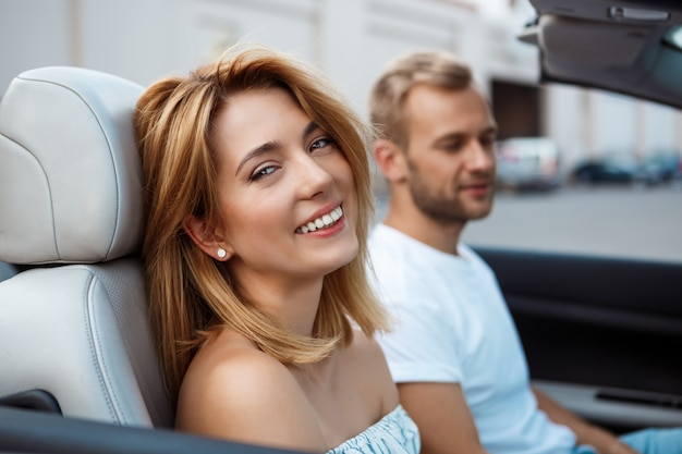 Giovani belle coppie che sorridono, sedendosi in automobile vicino al litorale.