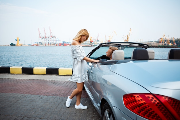 Giovani belle coppie che sorridono, sedendosi in automobile vicino al mare.