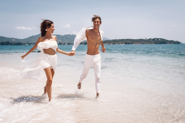 Giovani belle coppie della donna e dell'uomo in vestiti bianchi che corrono lungo la spiaggia