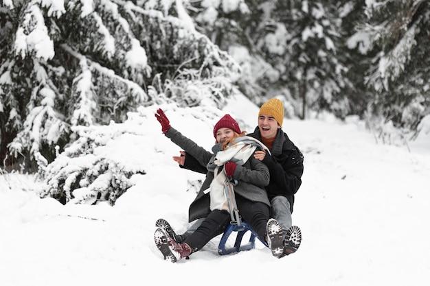Giovani belle coppie divertendosi sulla slitta