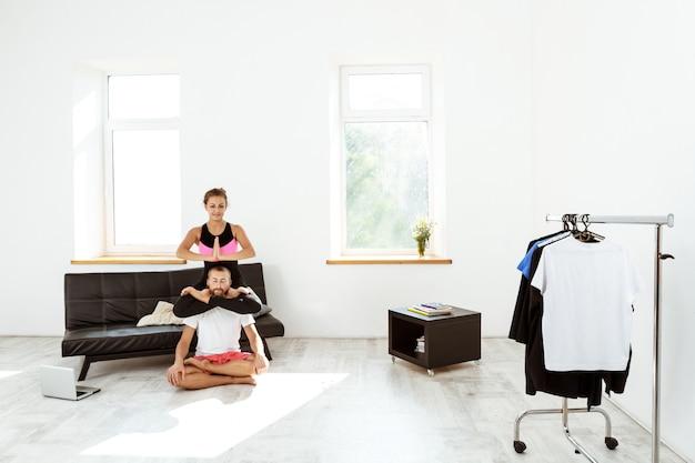 Giovani belle coppie sportive che meditano, praticando asana di yoga a casa.