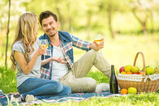 Giovani belle coppie vestite casual avendo picnic.