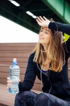 Giovani belle donne che riposano e che bevono acqua dopo avere fatto gli esercizi
