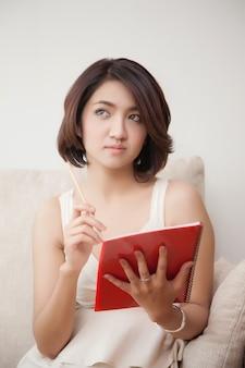 Giovani belle donne dell'asia che tengono libro e matita
