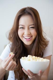 Giovani belle donne in possesso di una ciotola di popcorn