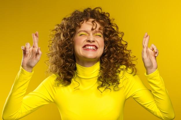 Giovani belle donne sorridenti con capelli ricci e incrocio le dita e augurando buona fortuna