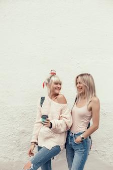 Giovani belle ragazze beve il caffè in un bicchiere per strada, ride e sorride