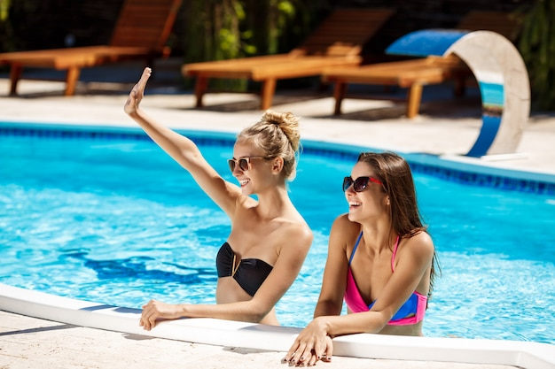 Giovani belle ragazze che sorridono, che accolgono, rilassandosi nella piscina.