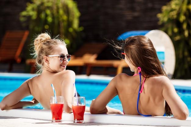 Giovani belle ragazze che sorridono, che parlano, che si rilassano nella piscina.