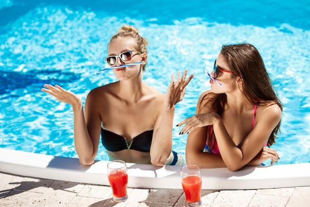 Giovani belle ragazze che sorridono, scherzano, parlano, si rilassano nella piscina.